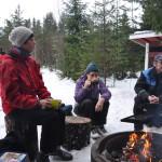 Koski 150 v- hiihtopäivänä satoi vettä, mutta kilometrejä kertyi n. 200, nuotiolla Seija Virtanen, Leena Tamminen ja Matti Tuomola.